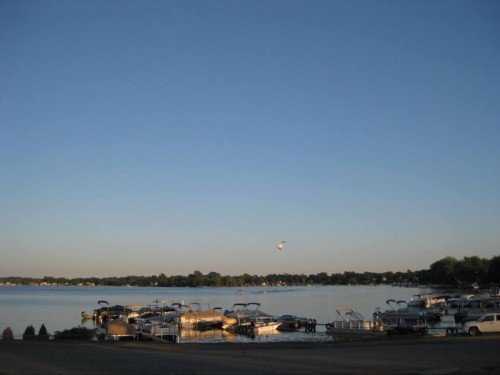 "Lake Whitmore, outside of Ann Arbor, Michigan: ""This stretch of lakeshore is also lined with chain-link fencing, but it allows approach almost to the water's edge. I walk up to the fence and grab links with each, hand. Leaning forward, I press my face into the wires and gaze upon a thin slice of moonlight cutting its way across gentle ripples. I can't reach you, I say silently. Can you hear me? I can't get through."""